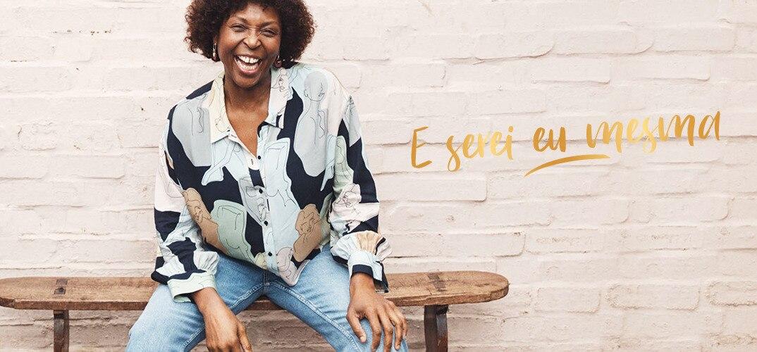Mulher confiante sentada num banco a sorrir