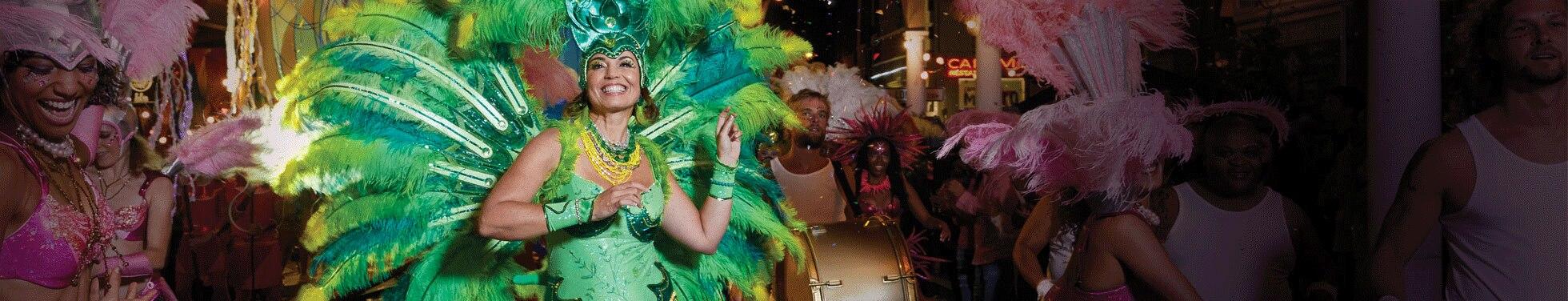 Жінки в зеленому пір'ї танцюють на карнавалі