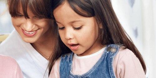 Huncut 3 éves kislány fordul oda egy felnőtthöz, miközben büszkén, ügyessége tudatában kinyit egy fürdőszobai fiókot