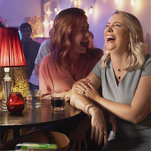 Couple of women laughing together in a bar