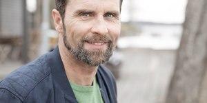 Muž v stredných rokoch s bradou sa usmieva do kamery