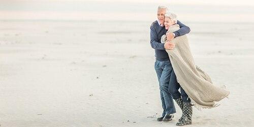 Elderly couple walking on the beach embracing
