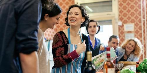 Een vrouwelijke kookdocente wordt omringd door nieuwsgierige leerlingen in een keuken.