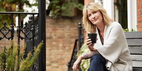 Mujer disfrutando de una taza de té en el porche de su casa de ladrillo