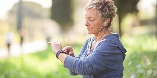 Tekačica s slušalkami preverja, koliko je ura na svoji ročni uri