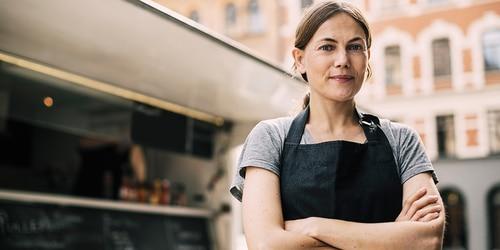 Vy framifrån av självsäker kvinnlig kock som står vid en streetfoodbil i en stad